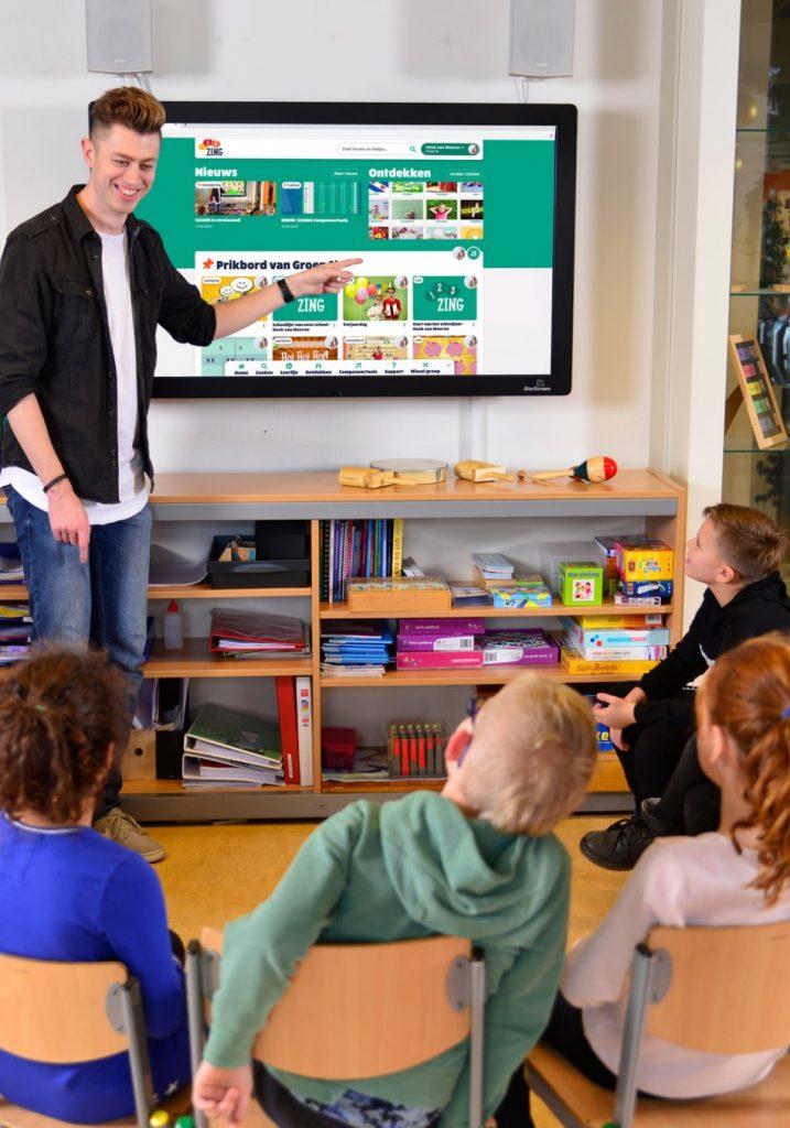 Leerkracht in de klas voor een digibord met de digitale muziekmethode