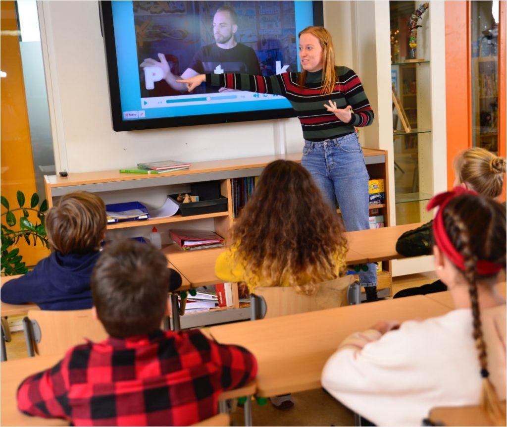 Juffrouw in de klas met digibord en kinderen zittend achter hun tafel