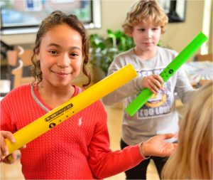 Meisje en jongen in klas met gekleurde boomwhacker