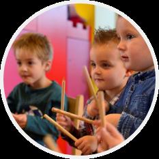 3 kinderen met een muziekinstrument in de klas