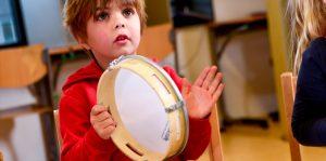 Jongetje in de klas spelend op een tamboerijn