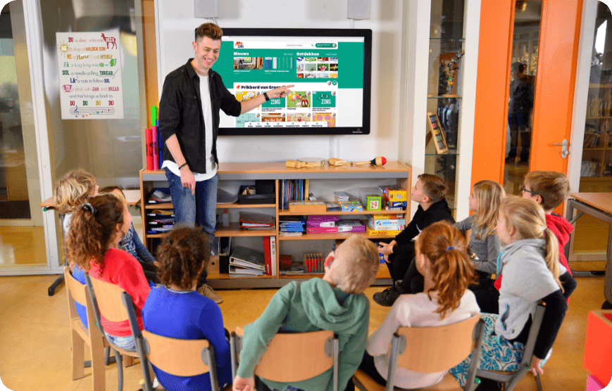Leerkracht voor digibord in de klas met componeertool prikbord en liedjes